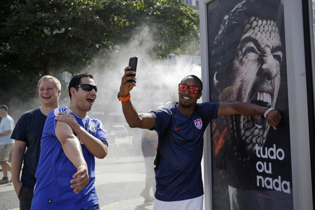 In this June 26, 2014 file photo, a U.S. soccer fan pretends that Uruguay's soccer striker Luis Suarez is biting him as he takes a selfie next to an Adidas advertisement featuring Suarez near Copacabana beach in Rio de Janeiro, Brazil. FIFA banned Suarez from all football activities for four months on Thursday for biting an opponent at the World Cup, a punishment that rules him out of the rest of the tournament. (Photo by Matt Dunham/AP Photo)