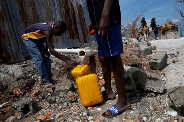 Men fill containers with water next to destroyed houses after Hurricane Matthew passes in Jeremie, Haiti, October 10, 2016. (Photo by Carlos Garcia Rawlins/Reuters)
