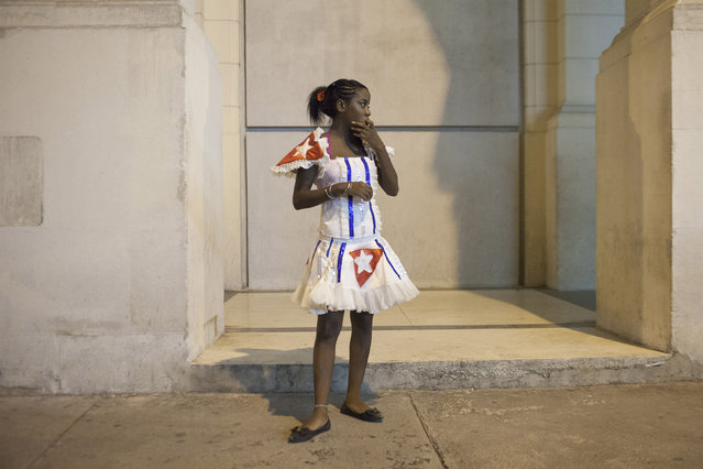 A dancer takes a break during the celebrations of the 54th anniversary of the creation of the Committees for the Defense of the Revolution (CDR) in Havana, September 28, 2014. (Photo by Alexandre Meneghini/Reuters)