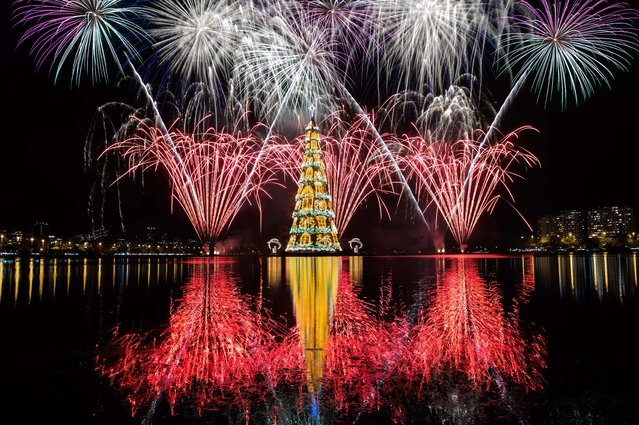 View of fireworks during the inauguration of an 85-meter-high floating Christmas tree at Rodrigo de Freitas lagoon in Rio de Janeiro, Brazil, on November 29, 2014. The world highest floating Christmas tree registered by the Guinness World Records was inaugurated for its 19th time Saturday night and will be illuminated by 3.1 million lights every night until the end of the year. (Photo by Yasuyoshi Chiba/AFP Photo)