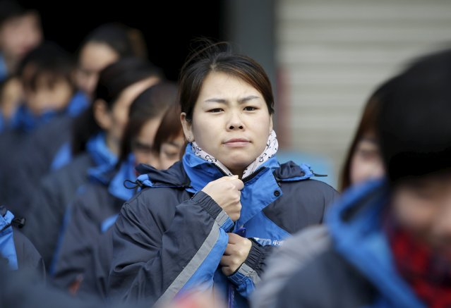 Workers listen to their line manager as he prepares them for the upcoming Singles Day shopping festival, at a sorting centre of Zhongtong (ZTO) Express, Chaoyang District, Beijing, November 8, 2015. (Photo by Jason Lee/Reuters)