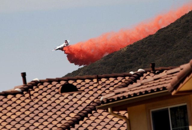 A firefighting aircraft drops fire retardant along a hill side near homes in Thousand Oaks, Calif. on Thursday, May 2, 2013. A wildfire fanned by gusty Santa Ana winds raged along the fringes of Southern California communities on Thursday, forcing evacuation of homes and a university while setting recreational vehicles ablaze. (Photo by Nick Ut/AP Photo)