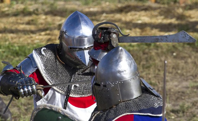 """A member of team Japan, left, fights against a Czech Republic contestant during the """"Battle of Nations"""" in Aigues-Mortes, southern France, Friday, May 10, 2013 where Middle Ages fans attend the historical medieval battle  competition. The championship will be attended by 22 national teams, which is twice the number it was last year. The battle lasts until May 12.(Photo by Philippe Farjon/AP Photo)"""