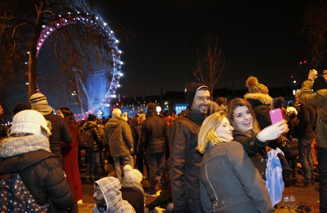Revellers take a selfie as they wait for the fireworks to start at the London Eye on the River Thames during New Year's celebrations in London December 31, 2014. (Photo by Suzanne Plunkett/Reuters)