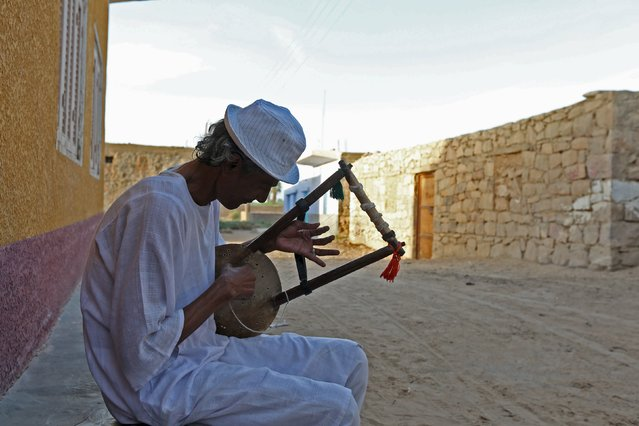 A man plays music on a traditional musical instrument in the Nubian village of Adindan near Aswan, south of Egypt, September 30, 2015. (Photo by Mohamed Abd El Ghany/Reuters)