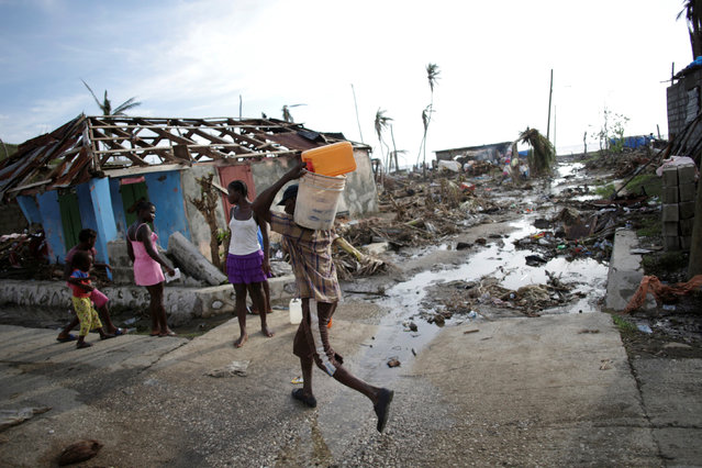 A man carries containers while walkiong next to a house affected by Hurricane Matthew in Damassins, Haiti, October 22, 2016. (Photo by Andres Martinez Casares/Reuters)