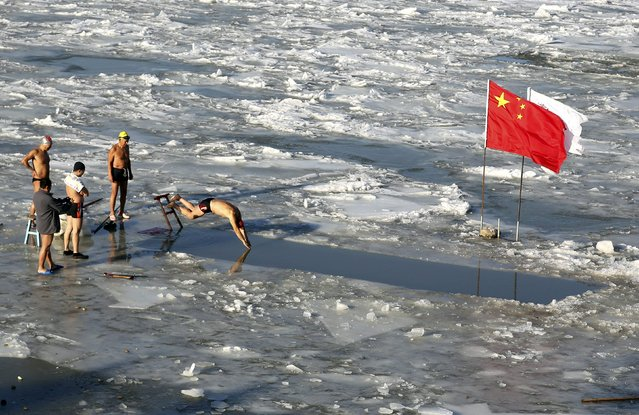 A winter swimmer jumps into icy water after breaking part of the frozen surface of the Amur river, in Heihe, Heilongjiang province, China, November 1, 2015. (Photo by Reuters/China Daily)