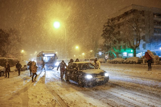 People push a car stranded in the snow in Madrid, Spain, late 08 January 2021. A red warning has been issued in Madrid as storm Filomena b​rought the heaviest snowfall in decades. (Photo by Rodrigo Jimenez/EPA/EFE)