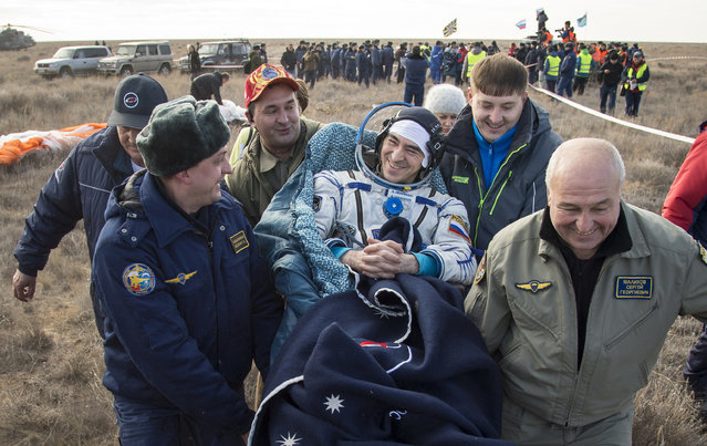 In this photo released by NASA, Russian cosmonaut Anatoly Ivanishin of Roscosmos is carried to a medical tent shortly after he is helped out of the Soyuz MS-01 spacecraft along with astronaut Kate Rubins and astronaut Takuya Onishi of the Japan Aerospace Exploration Agency (JAXA) who landed in a remote area near the town of Zhezkazgan, Kazakhstan Sunday, October 30, 2016. (Photo by Bill Ingalls/NASA via AP Photo)