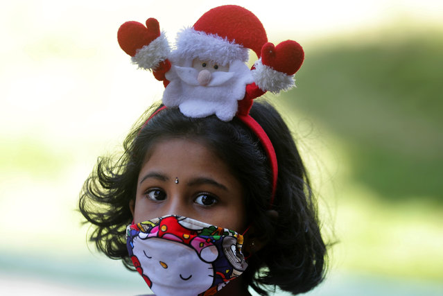 A Sri Lankan Christian girl wears a Santa hair band and a face mask as a precaution against the coronavirus as she arrives at a church to attend the Christmas mass in Colombo, Sri Lanka, Friday, December 25, 2020. (Photo by Eranga Jayawardena/AP Photo)