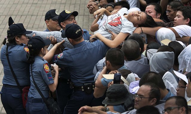 A woman is carried out from the crowd after she passed out as thousands of Filipinos wait for Pope Francis' arrival at the Cathedral Basilica of the Immaculate Conception in Manila, Philippines, Friday, January 16, 2015. Pope Francis celebrated the holy mass with bishops, priests, nuns, and seminarians as part of his Apostolic Mission to the Philippines. (Photo by Ron Soliman/AP Photo)
