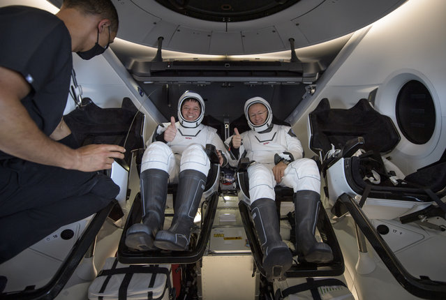 NASA astronauts Robert Behnken, left, and Douglas Hurley are seen inside the SpaceX Crew Dragon Endeavour spacecraft onboard the SpaceX GO Navigator recovery ship shortly after having landed in the Gulf of Mexico off the coast of Pensacola, Fla., Sunday, August 2, 2020. The Demo-2 test flight for NASA's Commercial Crew Program was the first to deliver astronauts to the International Space Station and return them safely to Earth onboard a commercially built and operated spacecraft. Behnken and Hurley returned after spending 64 days in space. (Photo by Bill Ingalls/NASA via AP Photo)