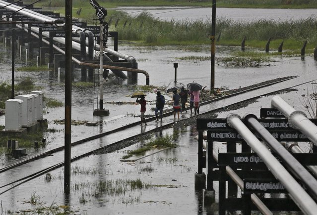 People walk on a flooded railway track as it rains in Chennai, India, December 6, 2015. (Photo by Anindito Mukherjee/Reuters)