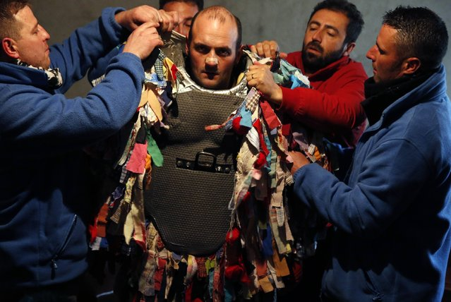 Raul Beites, 34, is helped by assistants as he is dressed as a Jarramplas during the Jarramplas traditional festival in Piornal, southwestern Spain, January 20, 2015. (Photo by Sergio Perez/Reuters)