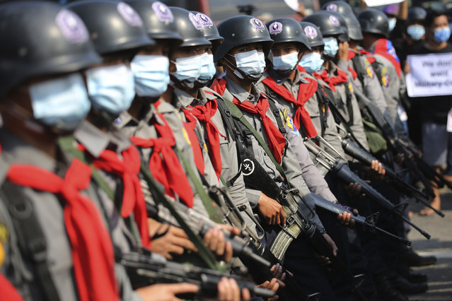 Armed riot police are seen near protesters in Naypyitaw, Myanmar on Monday, February 8, 2021. Tension in the confrontations between the authorities and demonstrators against last week's coup in Myanmar boiled over Monday, as police fired a water cannon at peaceful protesters in the capital Naypyitaw. (Photo by AP Photo/Stringer)