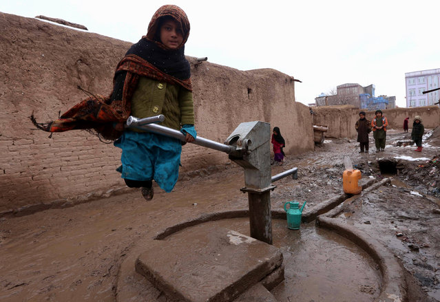 An Afghan woman fills containers with water near her temporary shelter at an internally displaced person's (IDP) camp on the outskirts of Herat, Afghanistan, January 21, 2015. Dozens of families are living in temporary shelters even in harsh winters and most depend on aid distributions by the United Nations High Commissioner for Refugees (UNHCR). (Photo by Jalil Rezayee/EPA)