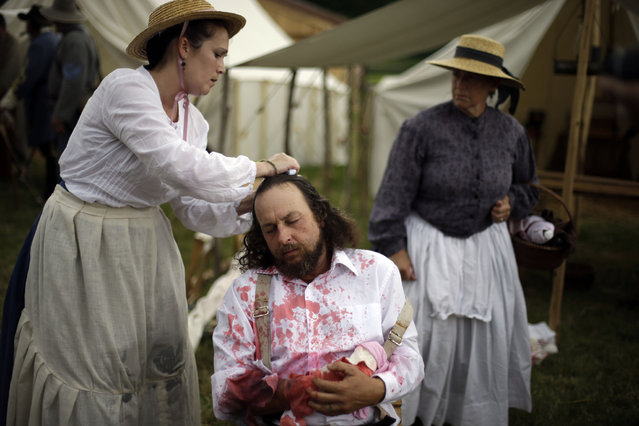 A Floridian portraying a wounded soldier from the 1st N.C. Infantry takes part of demonstration of a Confederate field hospital during ongoing activities commemorating the 150th anniversary of the Battle of Gettysburg, Friday, June 28, 2013, at the Daniel Lady Farm in Gettysburg, Pa.  Union forces turned away a Confederate advance in the pivotal battle of the Civil War fought July 1-3, 1863, which was also the war s bloodiest conflict with more than 51,000 casualties. (Photo by Matt Rourke/AP Photo)