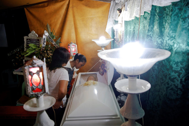 People look inside the coffin of a 7 year old girl killed at Tugatog public cemetery, as friends and relatives gather for the wake in Manila, Philippines October 25, 2016. (Photo by Damir Sagolj/Reuters)