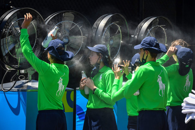 Ballkids cool off during day two of the Australian Open tennis tournament in Melbourne on February 9, 2021. (Photo by William West/AFP Photo)