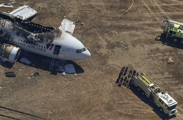Firefighters surround an Asiana Airlines Boeing 777 plane after it crashed while landing at San Francisco International Airport in California July 6, 2013. The plane with more than 300 people on board crashed on landing at San Francisco International Airport on Saturday after a flight from Seoul and burst into flames, and initial reports said two people were killed and over 70 injured. (Photo by Jed Jacobsohn/Reuters)