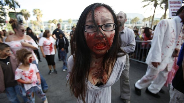 A woman dressed up as a zombie takes part in a zombie walk in the Gaslamp Quarter during the Comic Con International convention in San Diego, California July 13, 2012. (Photo by Mario Anzuoni/Reuters)