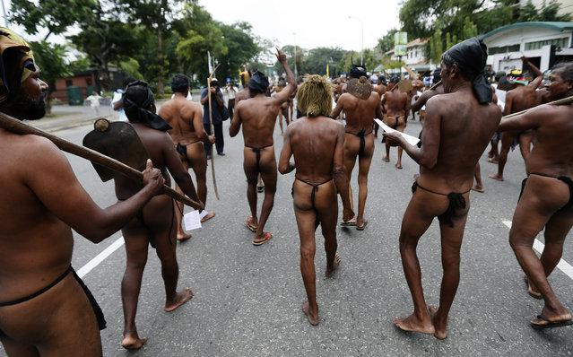 """Sri Lankan farmers in traditional outfits march during a protest against """"budget 2016"""" in Colombo, Sri Lanka December 17, 2015. The protest organized farmers of Sri Lanka against reducing the fertilizer subsidiary and reducing the guaranteed price for rice as well as against the budget proposal to reduce the farmers' pension by Sri Lankan Rupees 50. (Photo by Dinuka Liyanawatte/Reuters)"""