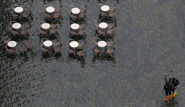 """People take a """"selfie"""" picture at the flooded St. Mark's Square during a period of seasonal high water and on the first day of carnival, in Venice February 1, 2015. (Photo by Stefano Rellandini/Reuters)"""