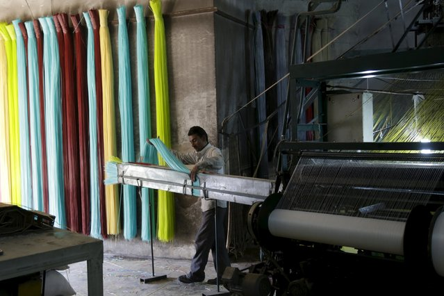 A man prepares plastic strings, used to produce mats, inside a mat factory in the rebel-controlled area of Maarshureen town in Idlib province, Syria, December 22, 2015. (Photo by Khalil Ashawi/Reuters)