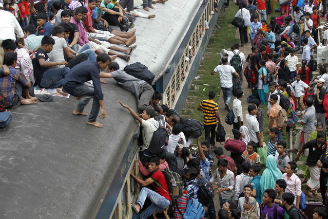Passengers try to climb on board an overcrowded train at a railway station in Dhaka August 8, 2013. Millions of residents in Dhaka are travelling home from the capital city to celebrate the Muslim Eid al-Fitr holiday, which marks the end of the holy fasting month of Ramadan. (Photo by Andrew Biraj/Reuters)