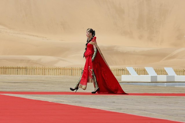 A model performs in Mongolia costumes in Xiangshawan Desert, also called Sounding Sand Desert on July 18, 2013 in Ordos of Inner Mongolia Autonomous Region, China. Xiangshawan is China's famous tourist resort in the desert. It is located along the middle section of Kubuqi Desert on the south tip of Dalate League under Ordos City. Sliding down from the 110-metre-high, 45-degree sand hill, running a course of 200 metres, the sands produce the sound of automobile engines, a natural phenomenon that nobody can explain. (Photo by Feng Li/Getty Images)