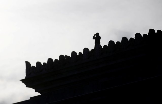 A member of law enforcement using binoculars is seen in silhouette on the roof of the Capitol Building, the day before a legislative session begins in Olympia, Washington, U.S. January 10, 2021. (Photo by Lindsey Wasson/Reuters)