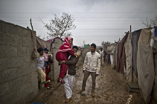 In this Saturday, February 7, 2015 photo, Pakistani Christian bride Dunya Yacob, 24, is carried by her cousin to her groom's makeshift home to attend her wedding ceremony at a slum home to Christian families on the outskirts of Islamabad, Pakistan. (Photo by Muhammed Muheisen/AP Photo)