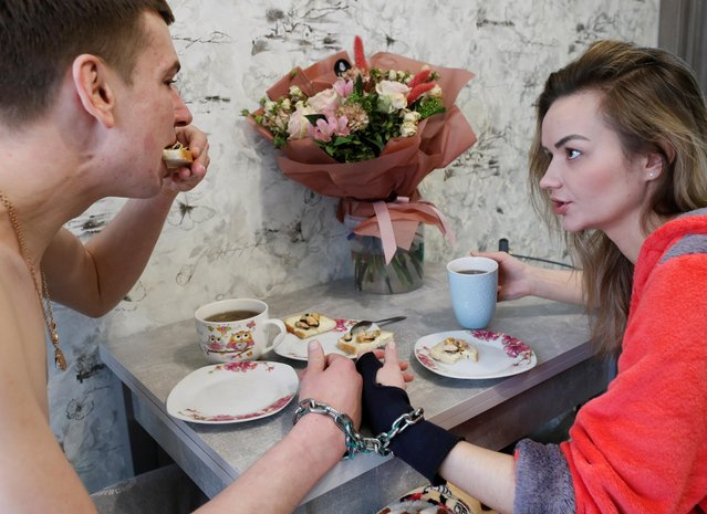 Alexandr Kudlay, 33, and Viktoria Pustovitova, 28, have breakfast in their apartment in Kharkiv, Ukraine on March 5, 2021. Tired of occasional break-ups, this Ukrainian couple found an unusual solution to stay inseparable. On St. Valentine's Day, they decided to handcuff their hands together for three months and began documenting their experience on social media. (Photo by Gleb Garanich/Reuters)