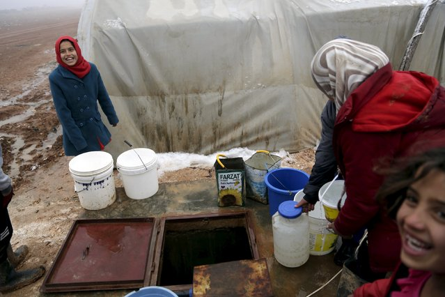 Internally displaced people fills buckets with water sourced from an underground well during the cold weather in Jerjnaz camp, in Idlib province, Syria, January 5, 2016. (Photo by Khalil Ashawi/Reuters)