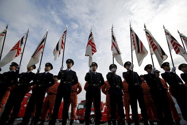 Members of the Tokyo fire department hold their flags before a New Year performance by the fire brigade in Tokyo, Japan, January 6, 2016. (Photo by Yuya Shino/Reuters)