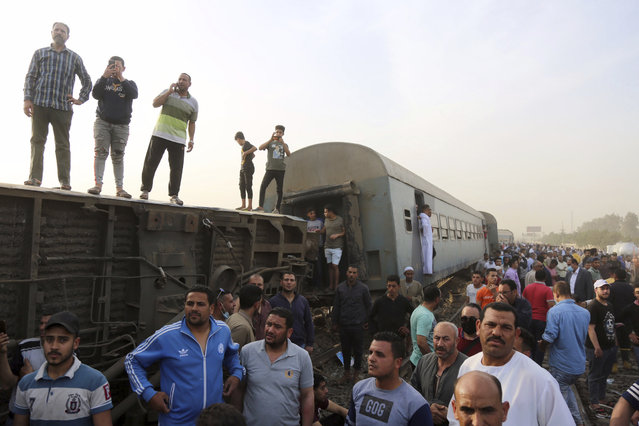 People gather at the site where a passenger train derailed injuring at least 100 people, in Banha, Qalyubia province, Egypt, Sunday, April 18, 2021. At least eight train wagons ran off the railway, the provincial governor's office said in a statement. (Photo by Fadel Dawood/AP Photo)