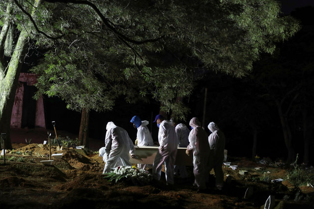 Gravediggers wearing protective suits carry a coffin as spotlights illuminate the graves during a night burial at Vila Formosa cemetery, amid the coronavirus disease (COVID-19) pandemic, in Sao Paulo, Brazil on April 28, 2021. (Photo by Amanda Perobelli/Reuters)