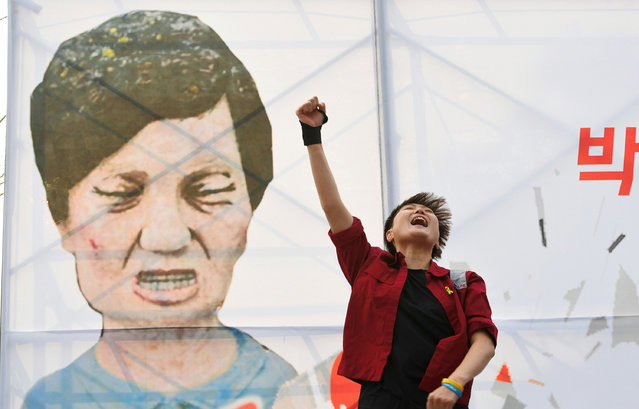 A protester shouts slogans in front of a caricature of South Korea's President Park Geun-Hye during a rally urging the impeachment of the president in Seoul on December 7, 2016. South Korea's scandal-hit Park said on December 6 she would accept the result of a looming and possibly lengthy impeachment process, but defied pressure to resign immediately. (Photo by Jung Yeon-Je/AFP Photo)