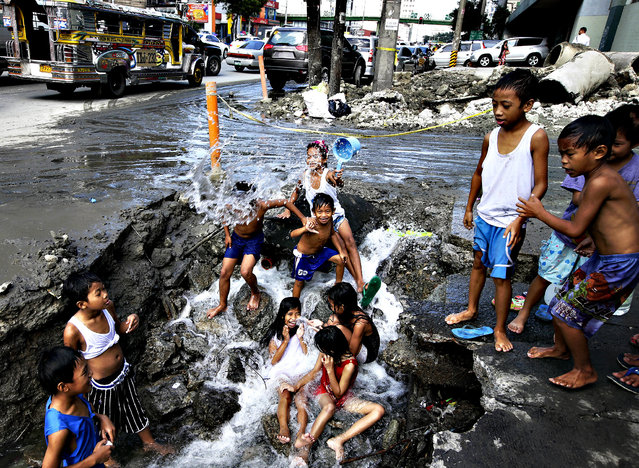 Children take advantage of a busted water pipe which was damaged overnight by a construction company as they take a bath Thursday, October 3, 2013 at suburban Quezon city northeast of Manila, Philippines. (Photo by Bullit Marquez/AP Photo)
