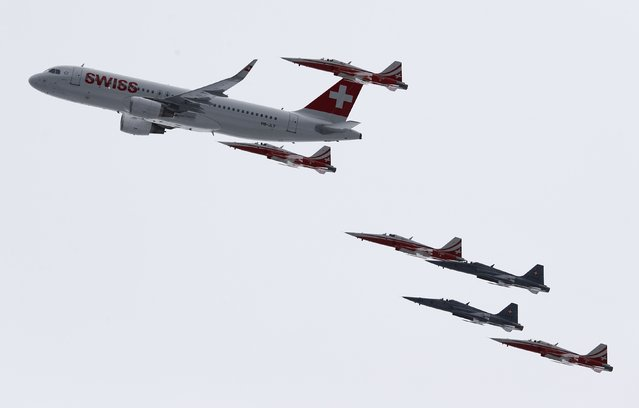 Members of the Swiss aerobatic team Patrouille Swiss fly in formation with a Swiss Airbus A 320 over the men's Alpine Skiing World Cup Super Combined in Wengen January 16, 2015. (Photo by Ruben Sprich/Reuters)