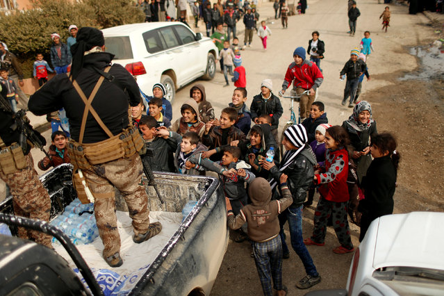 Iraqi soldiers distribute water to children outside a distribution point run by United Nations agencies at Zahra district, east of Mosul, Iraq December 8, 2016. (Photo by Ahmed Jadallah/Reuters)