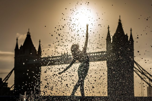 Rebecca Olarescu, a Masters screendance student at the London Contemporary Dance School (LCDS), performs during a dramatic sunrise at the fountains near Tower Bridge in London on April 27, 2021, ahead of International Dance Day on 29th April. First celebrated in 1982, International Dance Day has taken place every year since in anniversary celebration of the birth of Jean-Georges Noverre (1727-1810), the creator of modern ballet. (Photo by Guy Corbishley/Alamy Live News)