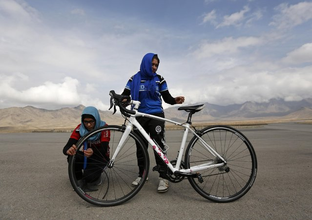 Masooma Alizada (L) and Frozan Rasooli (R), members of Afghanistan's Women's National Cycling Team prepare a bicycle before training on the outskirts of Kabul February 20, 2015. (Photo by Mohammad Ismail/Reuters)