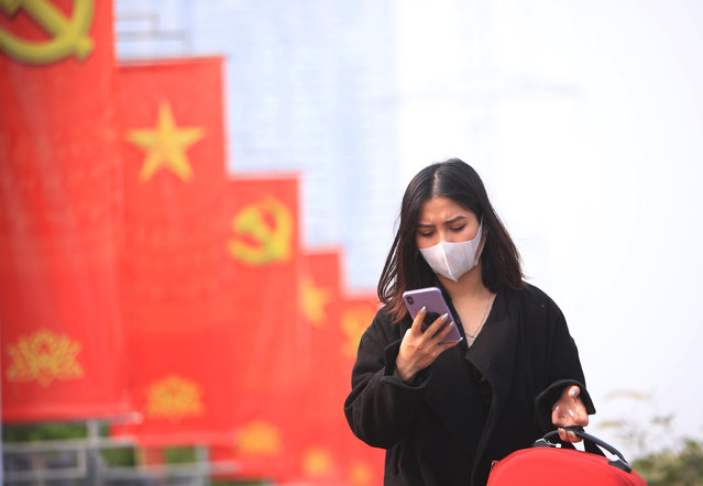 In this January 23, 2021 file photo, a woman wearing face mask looks at her phone in Hanoi, Vietnam.  Vietnam says it has discovered a new coronavirus variant that's a hybrid of strains first found in India and the U.K. The Vietnamese health minister made the announcement Saturday, May 29. (Photo by Hau Dinh/AP Photo/File)