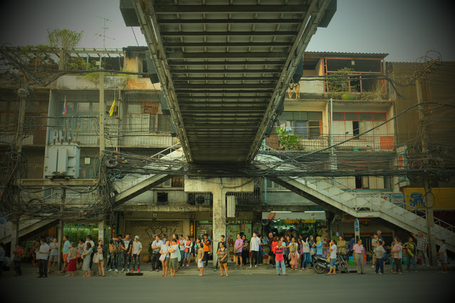 """Simon Cove, April winner and 2016 runner-up. """"Bus stop, rush hour, Bangkok. I was attracted by the symmetry of this Bangkok footbridge. The waiting people enhance the composition and show something of city life"""". MICK RYAN, JUDGE: Sometimes it is not the popular landmarks that grab our attention and it is good to explore the less obvious. I find this photograph mesmerising. A beautifully composed study yet with so many subject points – apartments, plants, aerials, wires – framed by the bridge and steps and people. The processing of the colour in retro-film tones adds calm to this chaotic scene. (Photo by Simon Cove/The Guardian)"""