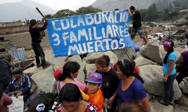 """People hold a sign that reads: """"Collaboration, three dead relatives"""" on the rocks that is covering a house, after a massive landslide in Chosica, March 24, 2015. (Photo by Mariana Bazo/Reuters)"""
