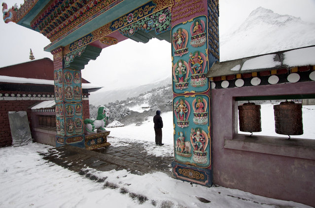In this Thursday, Feb. 26, 2015 photo, a local man stands in front of Tengboche monastery, a Tibetan Buddhist monastery of the Sherpa community, Nepal. (Photo by Tashi Sherpa/AP Photo)