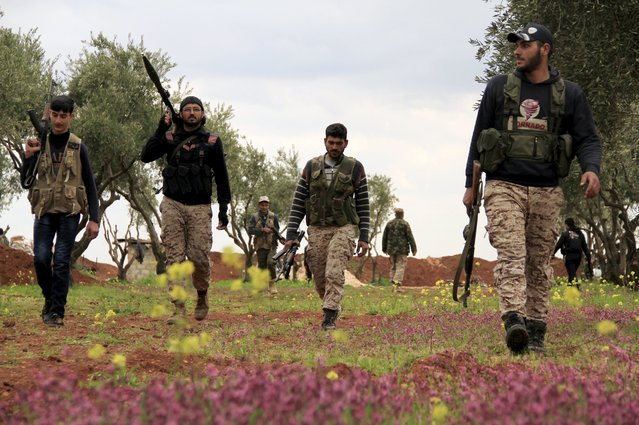 Rebel fighters of al-Jabha al-Shamiya (the Shamiya Front) walk along orchards on their way back from the frontline against Islamic State fighters on the outskirts of Mare town, north of Aleppo March 24, 2015. (Photo by Sultan Kitaz/Reuters)