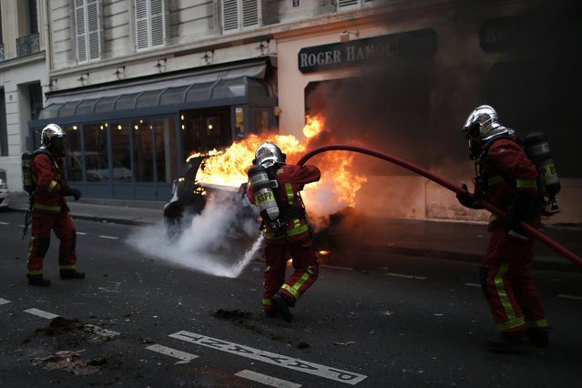 Firefighters put off a fire after clashes Saturday, December 8, 2018 in Paris. French riot police fired tear gas and water cannon in Paris on Saturday, trying to stop thousands of yellow-vested protesters from converging on the presidential palace to express their anger at high taxes and French President Emmanuel Macron. (Photo by Rafael Yaghobzadeh/AP Photo)