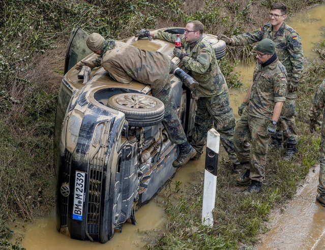 German soldiers work on a flooded car on a road in Erftstadt, Germany, Saturday, July 17, 2021. (Photo by Michael Probst/AP Photo)